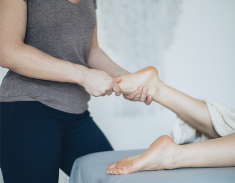 woman performing a reflexology foot massage on a client