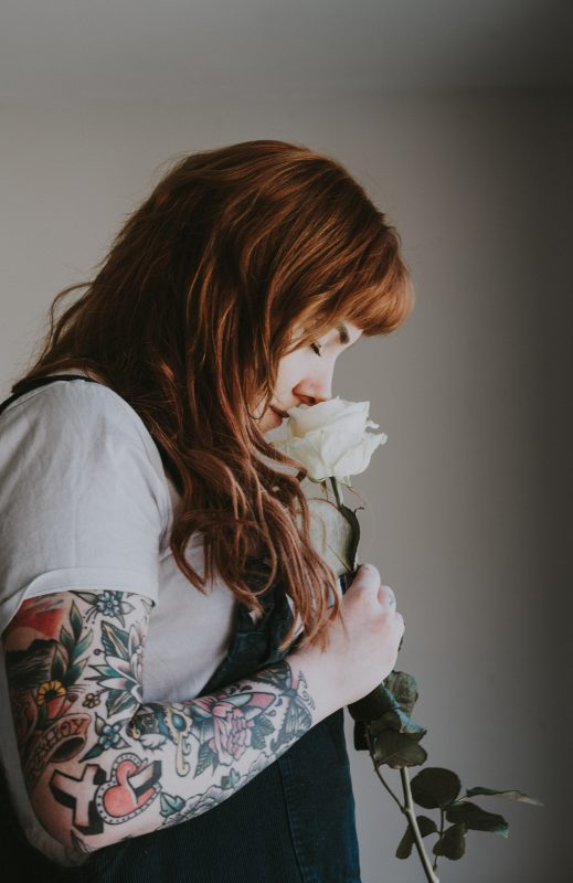 woman with tattoos smelling a rose to illustrate that smell can be a period symptom