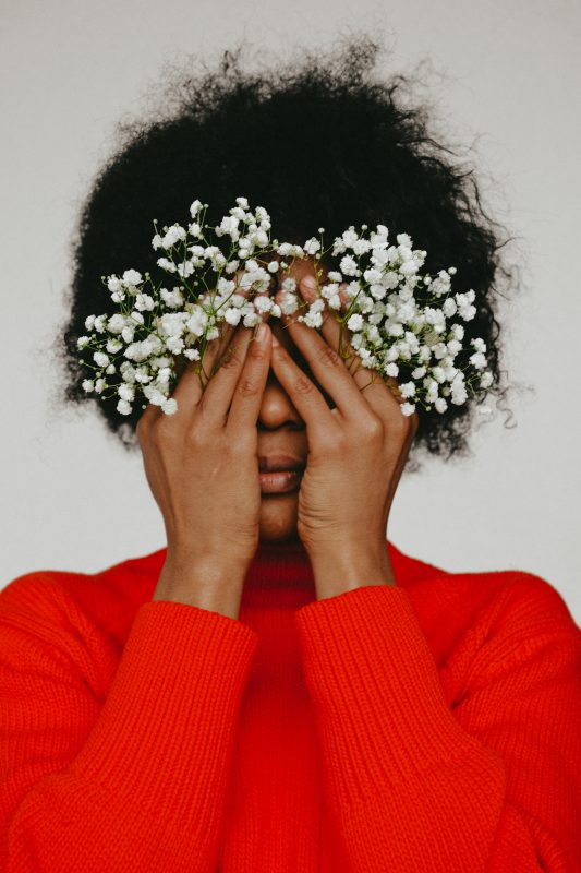 woman in red jumper covering her eyes holding gysophelia with embarrassment to illustrate that shame is not a period symptom