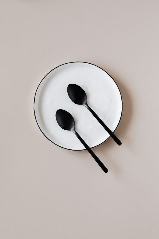 two tablespoons on a white plate on a beigi background to illustrate that a tablespoon of blood loss is a period symptom