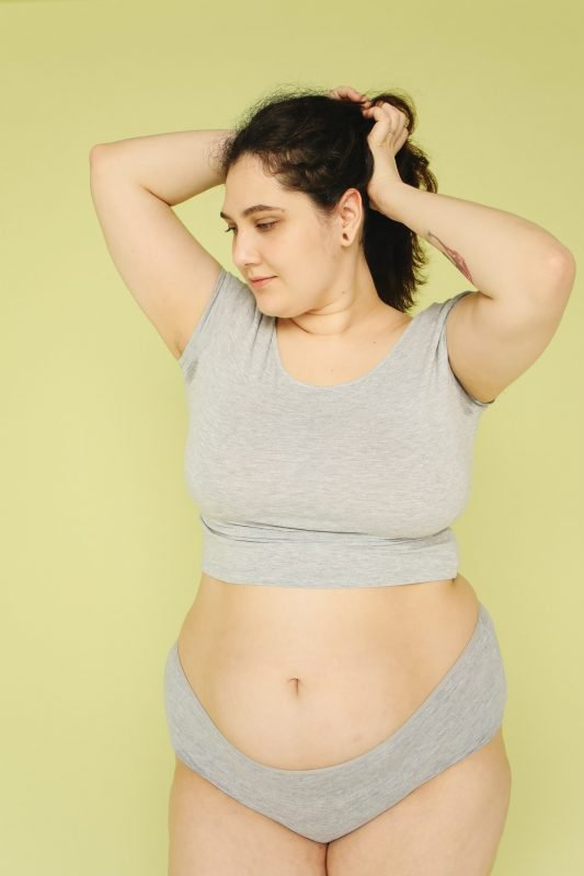 woman with sweat patches to illustrate that body odour is a period symptom