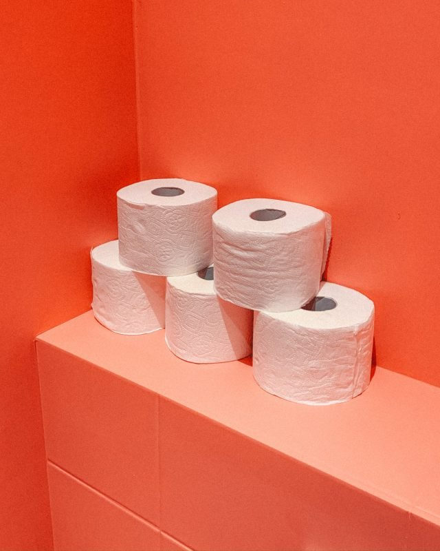pile of loo roll stacked against an orange wall to illustrate period symptoms