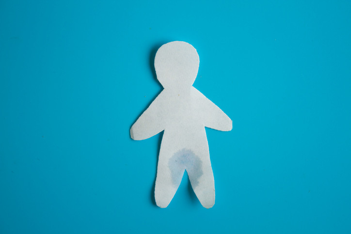 a paper figure with a wet crotch on a blue background to represent bladder weakness